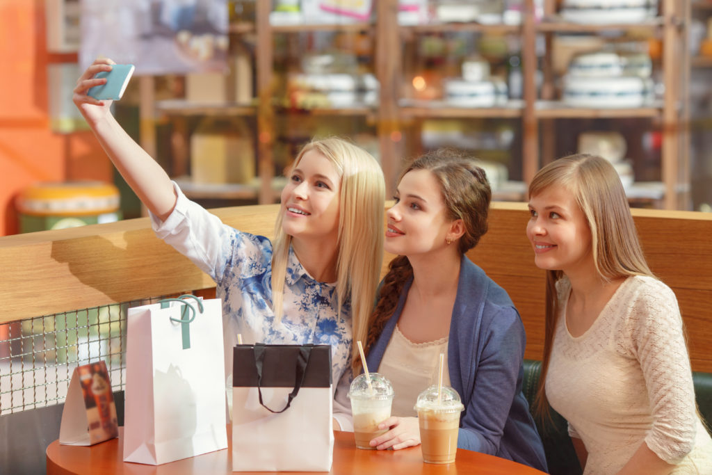 Generation Z girls taking a selfie in a coffee shop