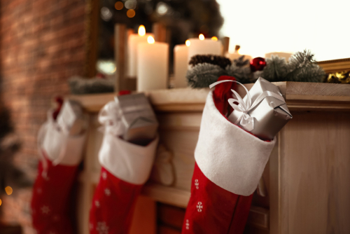 Stockings with gifts hung from a mantle